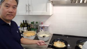 Bob Zhang cooking pancakes at the stove in the Ulman House kitchen