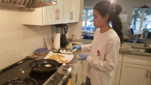Angel melting butter in a pan on the stove in the Ulman House kitchen