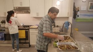 Riz in the Ulman House kitchen preparing food to be served