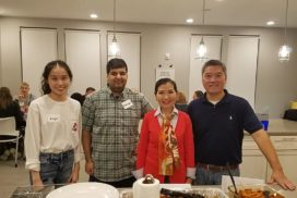 Angel, Riz, First Lady Yumi Hogan, and Bob Zhang stand in front of a counter covered in food